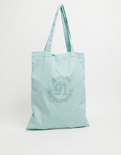 tote bag in pastel green with collegiate print