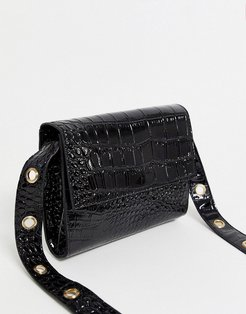 crossbody bag in black patent with gold eyelet detail strap