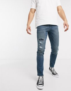 12.5oz slim jeans in vintage mid wash blue with rip and repair
