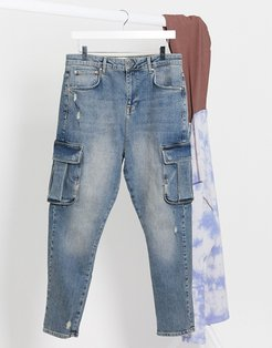 drop crotch jeans in dark wash blue tint with cargo pockets and abrasions